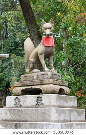 Kyoto, Japan - December 3, 2015: Fox holding a key in its mouth at Fushimi Inari Shrine in Kyoto, Japan. The shirne is the head shrine of Inari (the patron of business and merchants) in Japan.