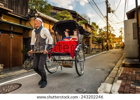 KYOTO, JAPAN - DECEMBER 29: Geishas ride in the back of a rickshaw through the Gion district on December 29, 2015 in Kyoto, Japan.