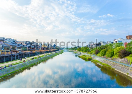 KYOTO, JAPAN - JUNE 20, 2015: Resting people and restaurants line the banks of the Kamo River on a blue sky day. Horizontal - stock photo
