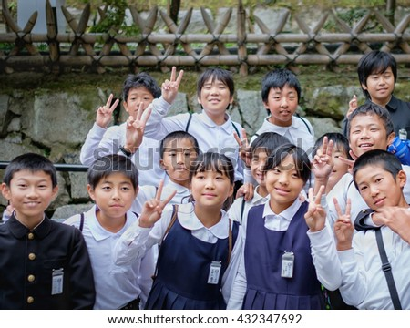 KYOTO,JAPAN - MARCH 24, 2015: Group of Japanese Elemantary school students in blue school uniform, looking at the photographer making a peace sign at Kiyomizu-dera Temple.. MARCH 24, 2015 Kyoto, Japan - stock photo