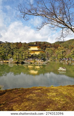 KYOTO, JAPAN - MARCH 10 2014: Old Japanese golden castle, Kinkakuji Temple (The Golden Pavilion) on a lake reflection and green garden in Kyoto.