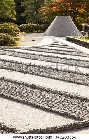 KYOTO, JAPAN - NOV 4, 2013: The grounds at the the Silver Pavilion complex, or Ginkakuji, in Kyoto are highlighted by a Zen garden of carefully raked sand and a perfect cone-shaped mountain of sand.  - stock photo