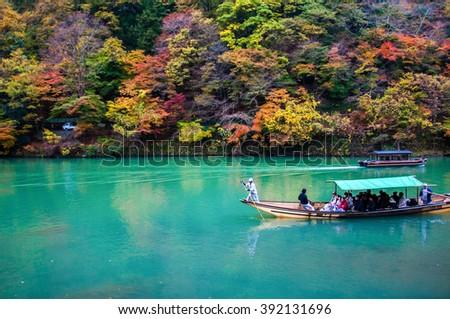Kyoto, Japan - NOV 23, 2012: Traditional tourist boat pass on the emerald color Katsura river along the beautiful autumn leaves in the cold tone, Arashiyama, Kyoto, Japan - stock photo