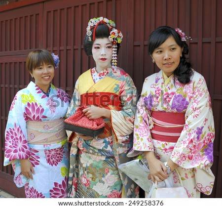 """KYOTO, JAPAN-NOVEMBER 4, 2014; A group of """"one day geisha"""" Japanese girls walking in a street and watching their friends .November 4, 2014 Kyoto,Japan - stock photo"""