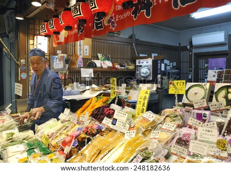 KYOTO, JAPAN - NOVEMBER 9, 2014: Fish vendor at food market stall in Nishiki market in Kyoto. Nishiki Market is famous in the city for high quality and gourmet foods. November 9, 2014 Kyoto, Japan - stock photo