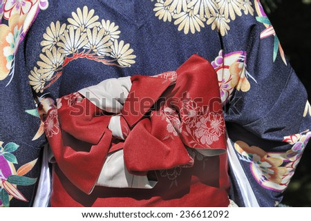 KYOTO, JAPAN - NOVEMBER 3: Geisha wearing a blue kimono with red munsuko and red obi. Kyoto is the capital of the geisha world.This is a traditional Japanese dress. November 3, 2014 Kyoto, Japan