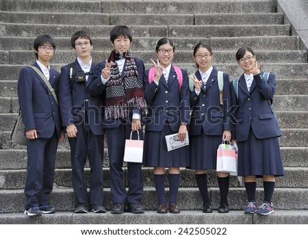 KYOTO,JAPAN - NOVEMBER 4, 2014: Group of Japanese high school students  in blue school uniform, looking at the photographer making a peace sign at Kiyomizu-dera Temple. November 4, 2014 Kyoto, Japan - stock photo