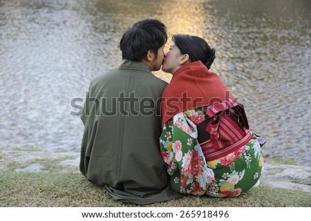 KYOTO, JAPAN-NOVEMBER 4, 2014;Young Japanese adult couple, both in kimono, kissing at the border of the Kamo river.November 4, 2014 Kyoto, Japan - stock photo