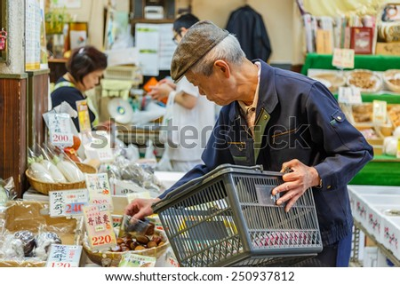 KYOTO, JAPAN - OCTOBER 23: Nishiki Market in Kyoto, Japan on October 23, 2014. Unidentified Japanese shop keeper prepares products in the shop for customer - stock photo