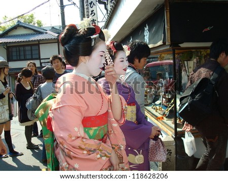 KYOTO -  MAY 1: Unidentified Geishas walking by an old street  on May 1, 2010 in Gion district, Kyoto, Japan. Geishas are girls skilled in traditional japanese arts. - stock photo