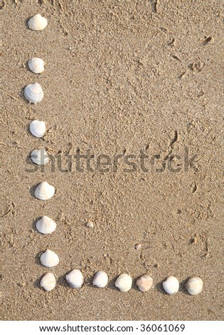 l letter symbol created from shells on a beach sand