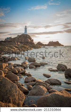 La Corbiere Lighthouse at sunset on Jersey in the Channel Islands, in the English Channel. - stock photo