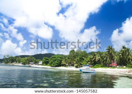 La Digue island, Seychelles, Anse la Reunion. White speedboat. Green forest.
