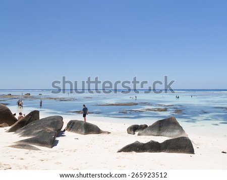 La Digue - November 8, 2014: Tourists rest and bathe on a  beach with coral sand and huge rocks at low tide on a clear day on the shores of the Indian Ocean November 8, 2014, La Digue, Seychelles - stock photo