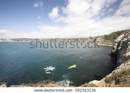 La Jolla Cove view of Kayaking in ocean waters and coastal shores - stock photo