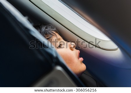 LA PAZ, BOLIVIA Circa March 2015: young child looking out of the airplane window - stock photo