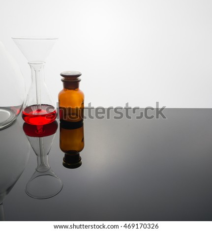Lab glassware on glass table with warm and white tone background.