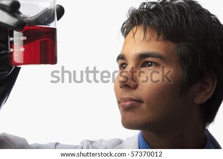 lab technician holding a beaker with fluid inside - stock photo