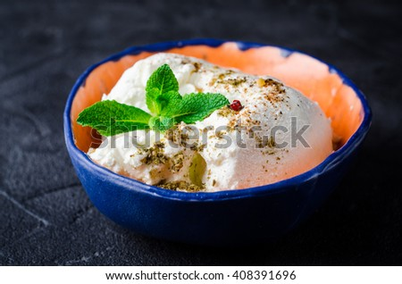 laban or labneh - homemade yogurt  cream cheese with spice and olive oil on dark background. Selective focus - stock photo