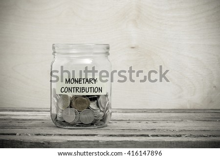 Label on a glass jar with the inscription - monetary contribution. Glass jar with coins. Financial concept on wooden background - stock photo
