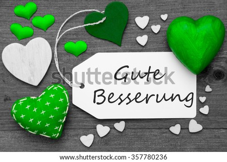 Label With Green Textile Hearts On Wooden Gray Background. German Text Gute Besserung Means Get Well Soon. Retro Or Vintage Style. Black And White Image With Colored Hot Spot. - stock photo