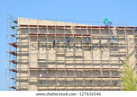labor working on scaffold in construction site