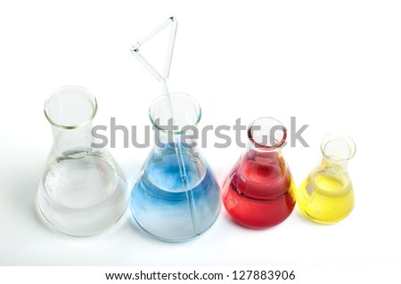Laboratory equipment and color chemicals on white background