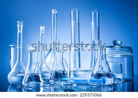 Laboratory equipment, bottles, flasks on blue background - stock photo