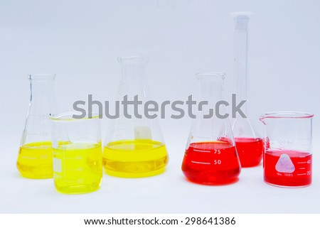 Laboratory flask with yellow and red liquid with glassware in white background - stock photo