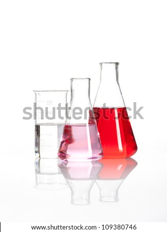 Laboratory flasks - Clear liquid mixed with a red colored chemical reagent, isolated - stock photo