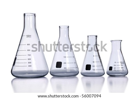 Laboratory flasks of different sizes with reflection on table - stock photo