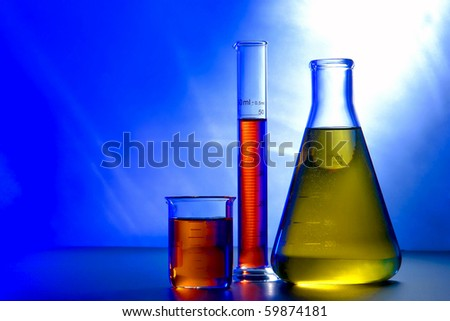 Laboratory glass conical Erlenmeyer flask filled with yellow liquid with beaker and graduated scientific cylinder full of red chemical solution for an experiment in a science research lab - stock photo