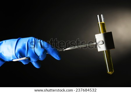 Laboratory glass test tube filled  color liquid held in specialized  clamp during  scientific experiment  - stock photo