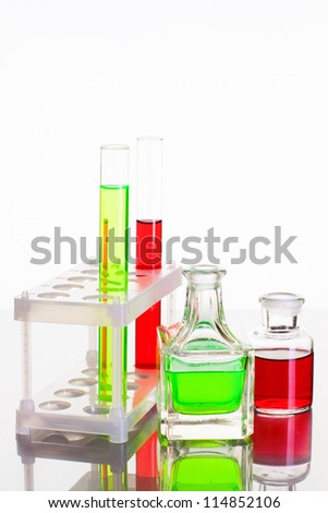 Laboratory glass test tubes with red and green liquid on white background