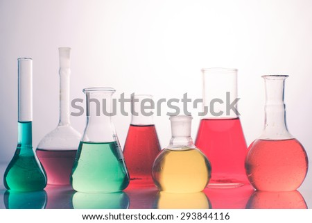 Laboratory glass with rainbow color liquids, chemistry still life