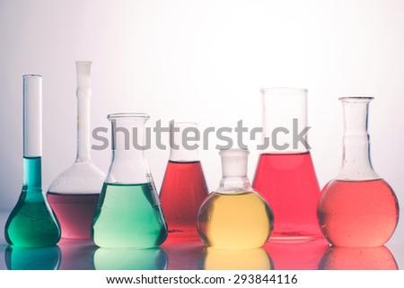 Laboratory glass with rainbow color liquids, chemistry still life - stock photo