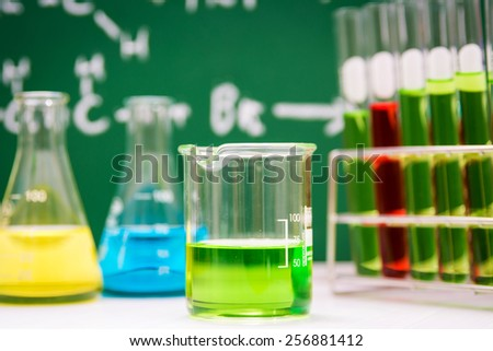 Laboratory glassware containing chemical liquid with green board background   - stock photo