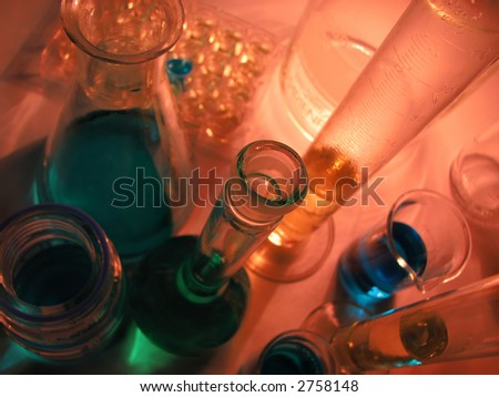 Laboratory glassware on red background in low light