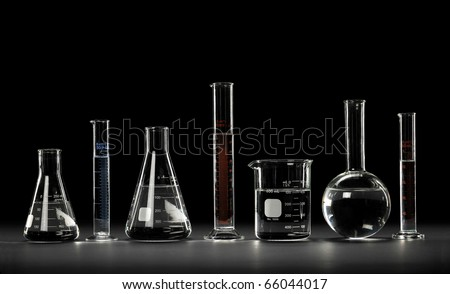 Laboratory glassware over black background and reflections on table - Clipping path on glassware - stock photo