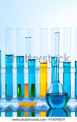Laboratory glassware with analyzing liquid over blue background - stock photo