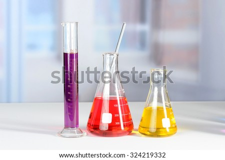 Laboratory glassware with colored liquids on lab table - stock photo