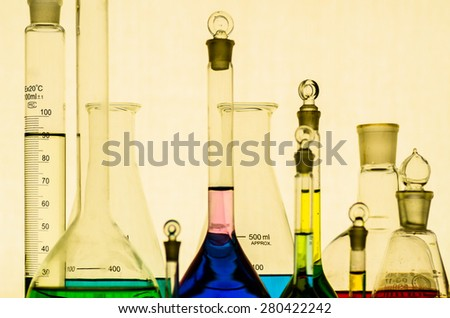 Laboratory glassware with liquids of different colors - stock photo