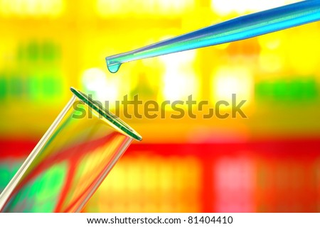 Laboratory pipette with drop of blue liquid chemical solution over glass test tube for an experiment in a science research lab - stock photo