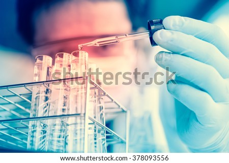 Laboratory pipette with drop of liquid over glass test tubes for an experiment in a science research lab .Man wears protective goggles - stock photo