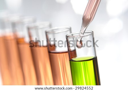 Laboratory pipette with drop of pink liquid over glass test tubes filled with green chemical solution for an experiment in a science research lab - stock photo