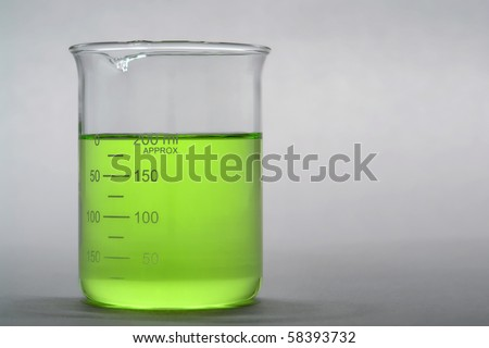 Laboratory scientific beaker filled with green liquid for an experiment in a science research lab - stock photo