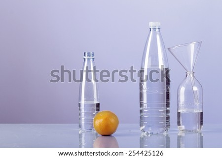 Laboratory shot of water bottles and dishes together with the fresh orange, representing fruit processing, mixing or genetic modification - stock photo