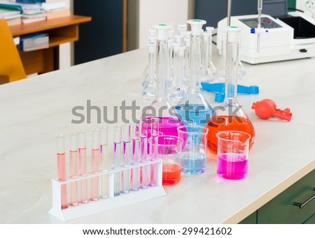 Laboratory vessels prepared for scientific experiment, filled with colourful liquids. - stock photo