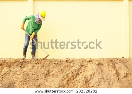 Laborer digging with hoe on construction site - stock photo