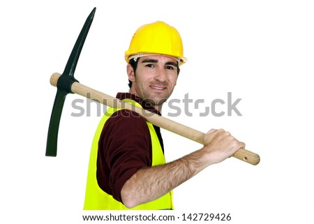 Laborer with pickaxe on his shoulder - stock photo